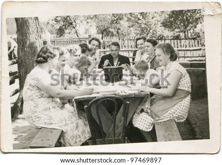 Vintage photo of big happy family dining outdoor (fifties) - stock photo