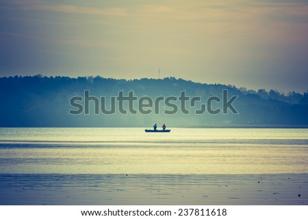 vintage photo of boat on lake at sunset - stock photo