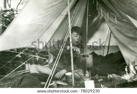 Vintage photo of boy camping (fifties) - stock photo
