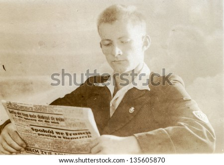 Vintage photo of boy reading a newspaper (thirties) - stock photo