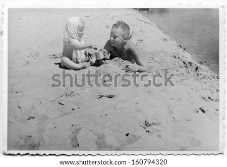 Vintage photo of brother and little sister on beach - fifties - stock photo