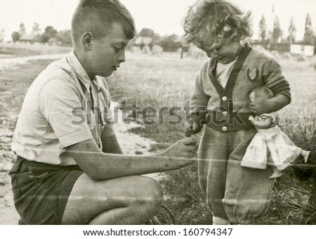 Vintage photo of brother and little sister with doll - fifties