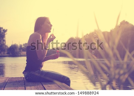 Vintage photo of bubble blower young woman at lake - stock photo