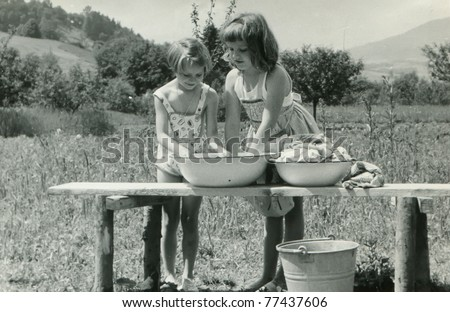 Vintage photo of children doing laundry outdoor (fifties) - stock photo