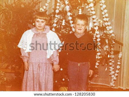 Vintage photo of children near Christmas tree, early eighties - stock photo