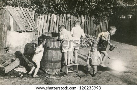 Vintage photo of children playing with big barrel (fifties)
