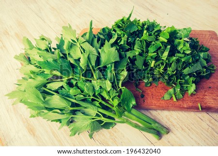 vintage photo of chopped parsley leaf on a wooden table - stock photo
