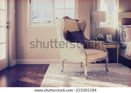vintage photo of classic chair with brown pillow on carpet in luxury bedroom interior - stock photo