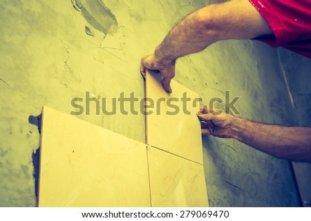 Vintage photo of construction mason man hands on tiles work with cement mortar - stock photo