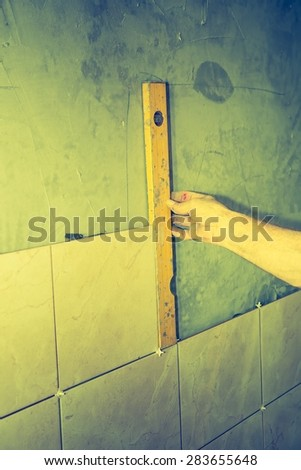 Vintage photo of construction mason man hands on tiles work with spirit level - stock photo