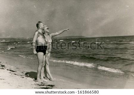 Vintage photo of couple on beach, fifties - stock photo