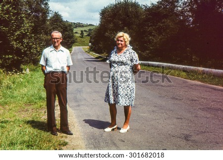 Vintage photo of couple on tar road (early 1970's) - stock photo