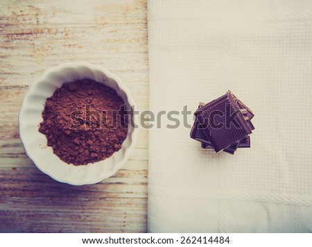 Vintage photo of cubes of chocolate and a bowl of cocoa - stock photo