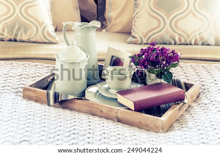 Vintage photo of decorative tray with book,tea set and flower on the bed - stock photo
