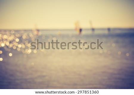 Vintage photo of defocused seascape with windsurfers on sea surface. Blurry landscape useful as background - stock photo