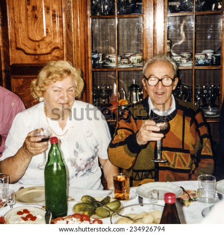 Vintage photo of elderly couple's wedding anniversary, eighties - stock photo