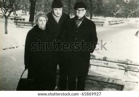 Vintage photo of elderly couple with son in park (winter) -sixties - stock photo