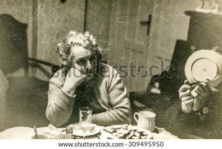Vintage photo of elderly woman during a family dinner, 1950's - stock photo