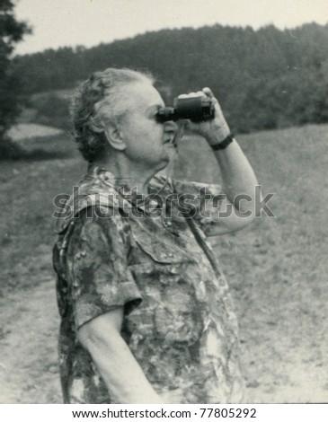 Vintage photo of elderly woman looking by binoculars (fifties) - stock photo