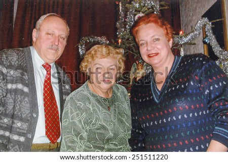 Vintage photo of elderly woman with her son and daughter in law in front of Christmas tree, nineties - stock photo