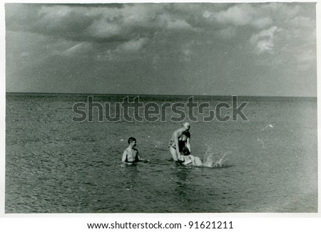 Vintage photo of family bathing in sea (fifties) - stock photo
