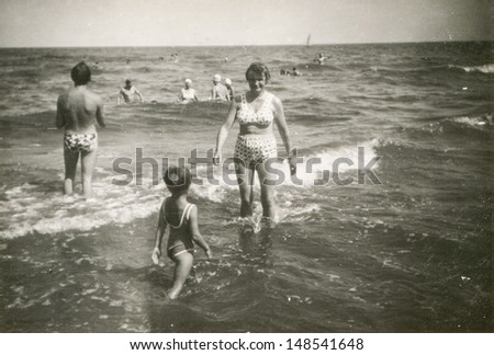 Vintage photo of family bathing in sea, sixties - stock photo