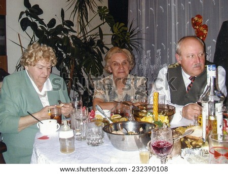 Vintage photo of family during a holiday dinner, eighties - stock photo
