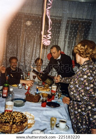 Vintage photo of family enjoying wedding anniversary party, early eighties - stock photo