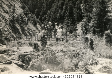 Vintage photo of family (grand father, mother and daughter) walking in mountains(sixties) - stock photo