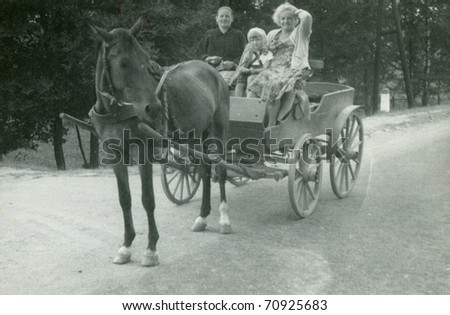 Vintage photo of family traveling in horse-drawn carriage (sixties) - stock photo