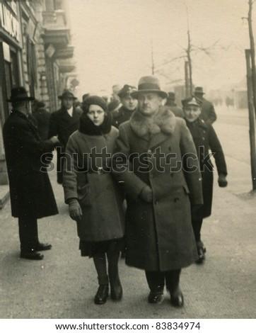 Vintage photo of family walking on the street (1936) - stock photo