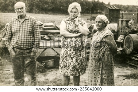 Vintage photo of farmers family (elderly parents and adult daughter) on farm, sixties - stock photo