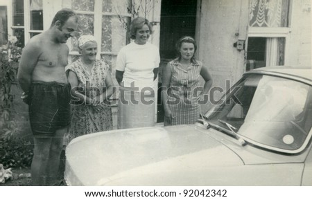 Vintage photo of farmers' family looking at a car (fifties) - stock photo