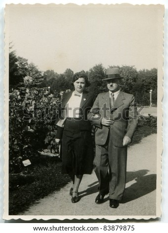 Vintage photo of father and daughter walking on the street (thirties) - stock photo