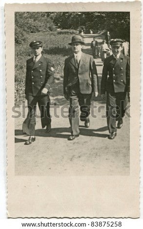 Vintage photo of father and sons in school uniforms walking on the street (thirties)