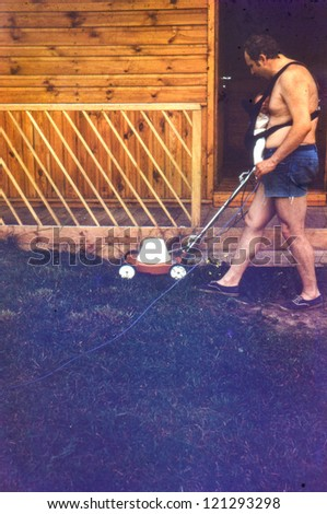 Vintage photo of father with baby daughter in baby carrier mowing grass (1981) - stock photo