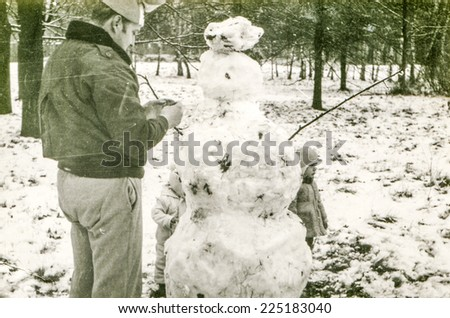 Vintage photo of father with daughter building a snowman, early eighties