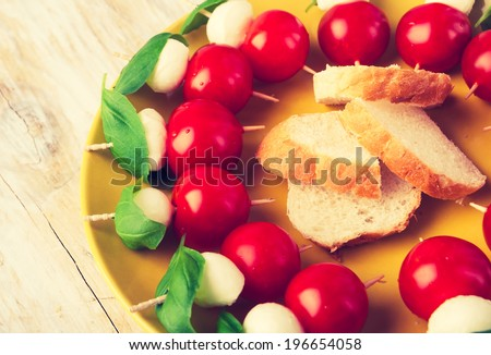 vintage photo of finger foods of mozzarella, tomatoes and fresh basil - stock photo