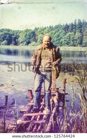 Vintage photo of fisherman at lakeside (seventies) - stock photo