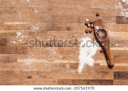 Vintage photo of flour, nuts and bake item on the wooden working desk of dirty top. Composition of bakery products for coffee shop. Copy space. - stock photo