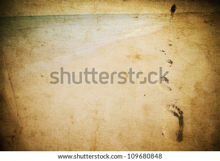 Vintage photo of footprints on beach - stock photo