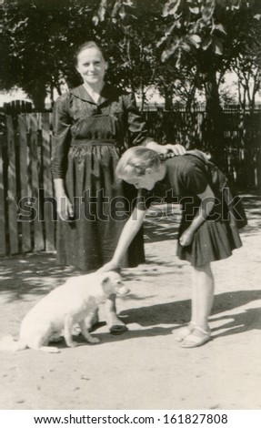 Vintage photo of grandmother and granddaughter with a dog, fifties