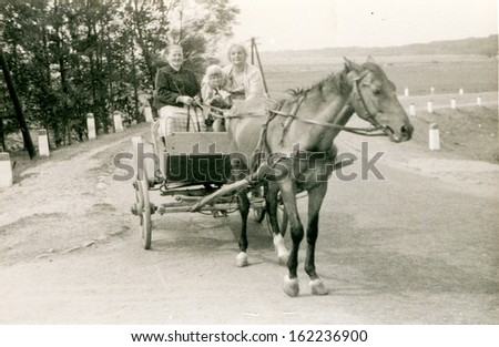 Vintage photo of grandmother, mother and little daughter traveling by horse-drawn carriage, fifties