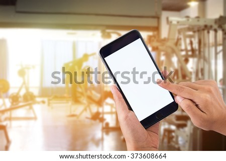 Vintage photo of Hand holding smartphone device at gym fitness club background at morning sunrise. - stock photo