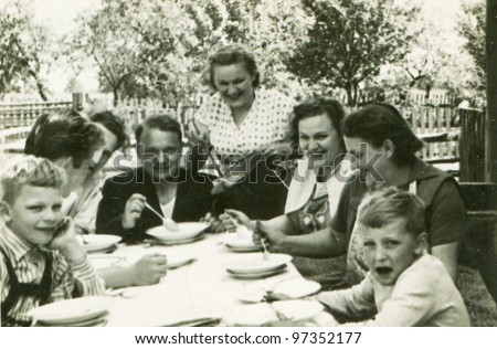 Vintage photo of happy family dining outdoor (fifties) - stock photo