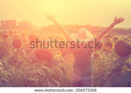 Vintage photo of happy woman in sunflower fields - stock photo