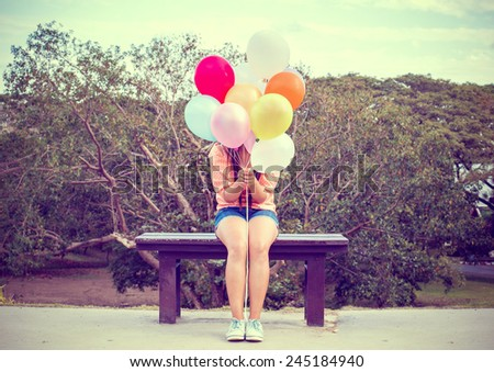 Vintage photo of  Happy young woman holding colorful balloons and sitting on bench - stock photo