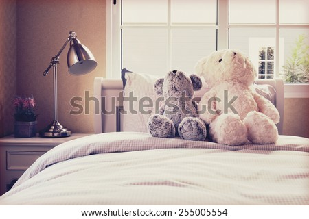 Vintage photo of kids room with dolls and pillows on bed and bedside table lamp - stock photo