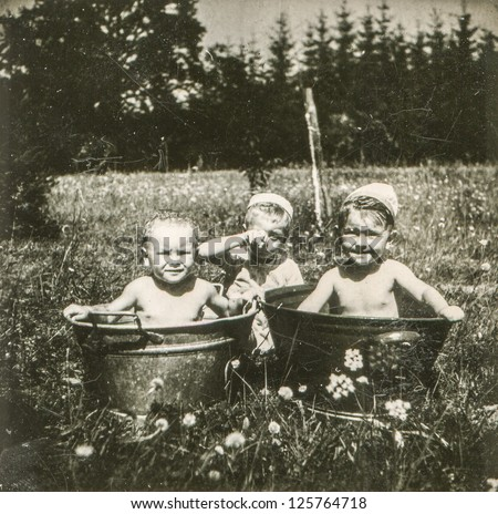 Vintage photo of little children bathing in wash tubs outdoor (early fifties) - stock photo