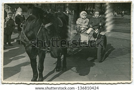 Vintage photo of little girl and boy on pony cart (fifties) - stock photo